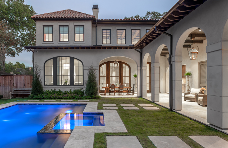 Architectural exterior elevation photograph of a Tanglewood residence from backyard over pool into arched walk way with outdoor dineing and seating area overlooking the pool